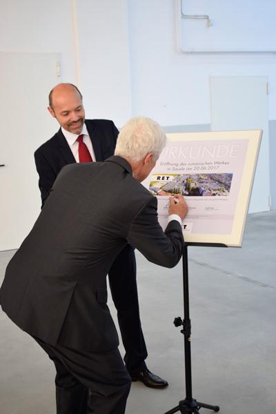 Geschäftsführer Hubert Reiff unterschreibt im Beisein von Betriebsleiter Tudor Garbacea die Eröffnungsurkunde